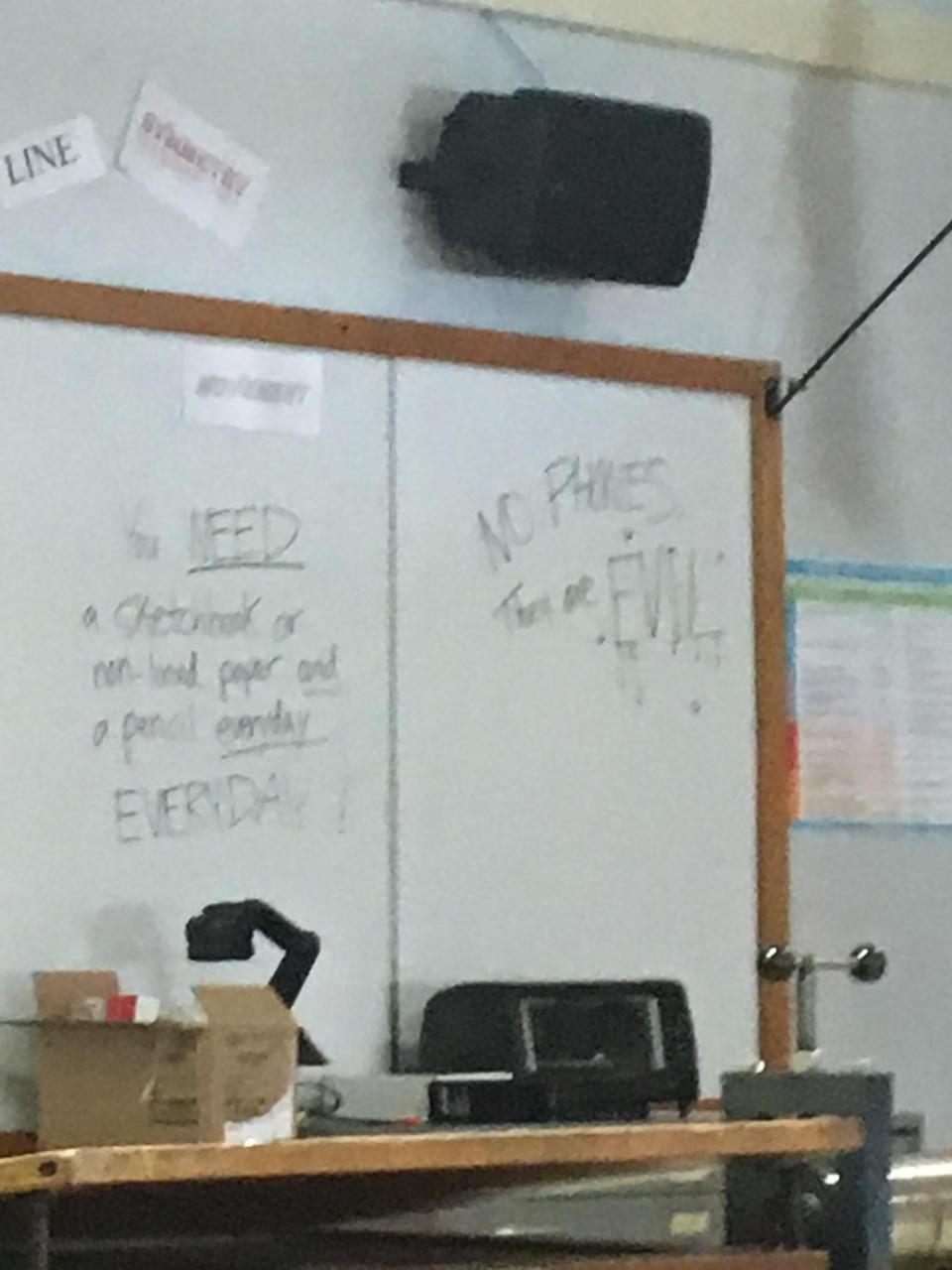 "Sorry for garbage picture, it says ""NO PHONES; They are EVIL!"" Found in my art class."